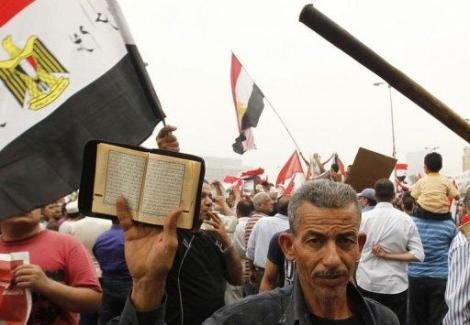 A supporter of Muslim Brotherhood candidate Mohammed Mursi holds up a copy of the Koran